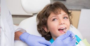 Young boy getting his teeth examined