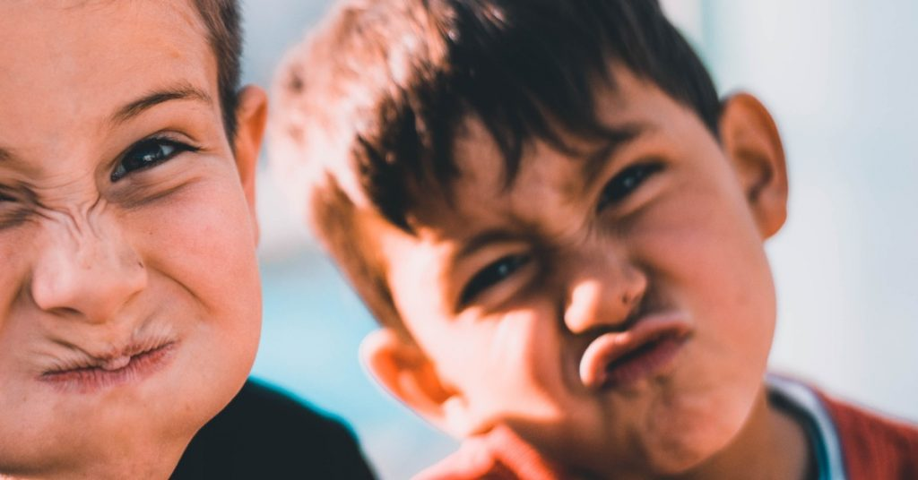 Two young boys making funny faces