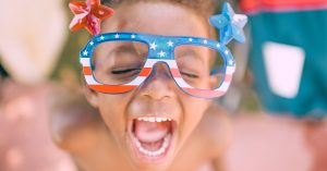 Young boy smiling with colorful glasses on