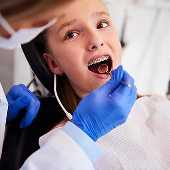 Young girl getting her teeth examined