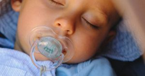 Little boy sleeping with a pacifier